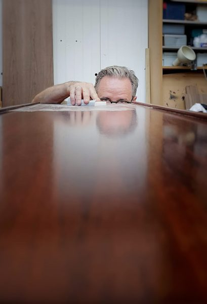 sam brown furniture hand finishing a rosewood table